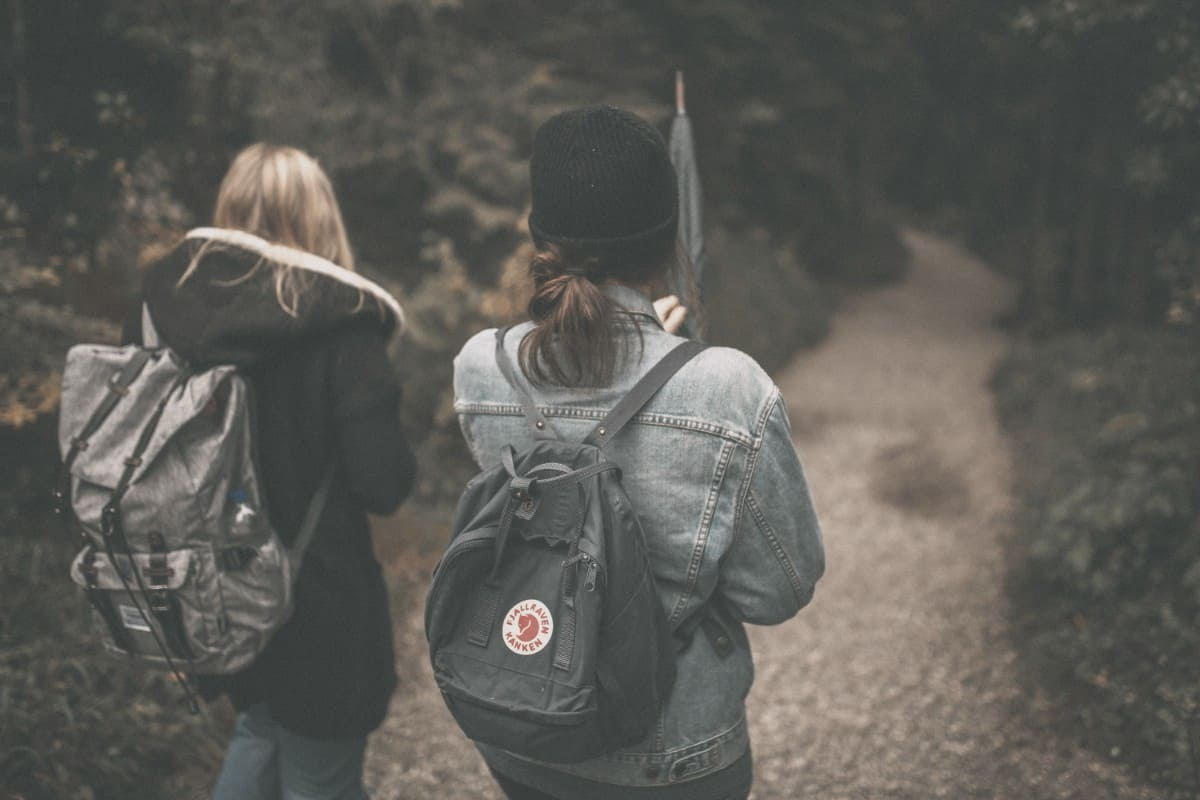 Women wear backpacks during hiking